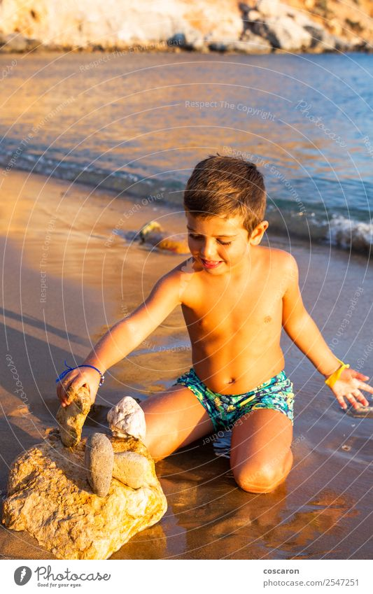 Kleines Kind, das am Strand mit Steinen baut. Lifestyle Freude Glück Spielen Ferien & Urlaub & Reisen Tourismus Sommer Sonne Meer Mensch maskulin Baby Kleinkind