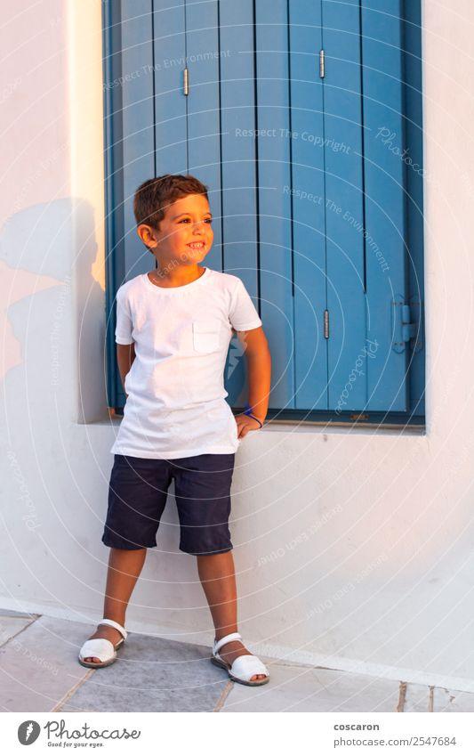 Süßes Kind in der Nähe eines blauen Holzfensters bei Sonnenuntergang Lifestyle Design Glück schön Ferien & Urlaub & Reisen Sommer Insel Haus Mensch Baby