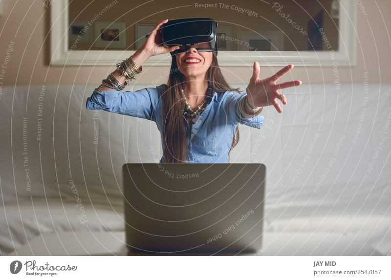 Frau erlebt Virtual Reality zu Hause Lifestyle Glück Freizeit & Hobby Spielen Häusliches Leben Wohnzimmer Entertainment Industrie Telefon Headset