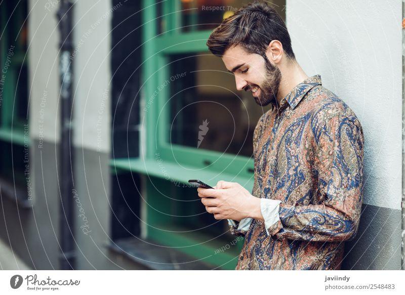 Junger lächelnder Mann schaut auf sein Smartphone auf der Straße. Lifestyle Stil schön Haare & Frisuren Telefon PDA Mensch maskulin Junger Mann Jugendliche