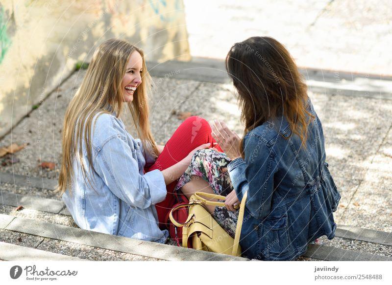 Zwei junge Frauen, die auf städtischen Stufen reden und lachen. Lifestyle Stil Freude Glück schön sprechen Mensch feminin Junge Frau Jugendliche Erwachsene