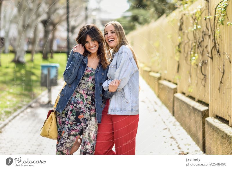 Zwei glückliche junge Frauenfreunde, die sich auf der Straße umarmen. Lifestyle Stil Freude Glück schön Mensch feminin Junge Frau Jugendliche Erwachsene