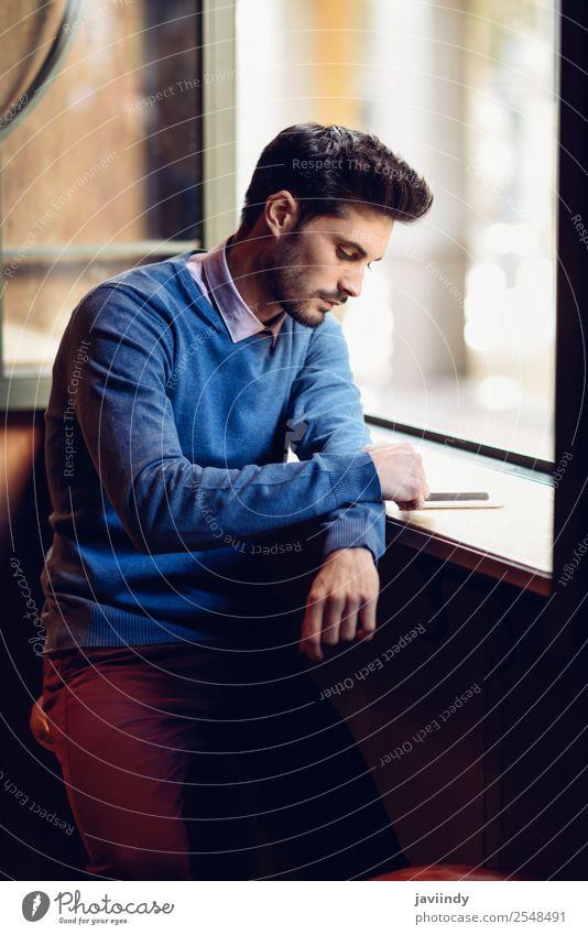 Ein Typ mit blauem Pullover schaut auf sein Smartphone in einer Bar. Lifestyle Stil schön Haare & Frisuren Telefon PDA Mensch maskulin Junger Mann Jugendliche