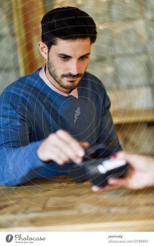 Hand haltendes Smartphone, das auf dem EDC-Gerät bezahlt. kaufen Geld Geldinstitut Business Telefon PDA Technik & Technologie Mensch maskulin Junger Mann