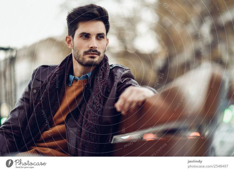 Nachdenklicher junger Mann, der auf einer städtischen Bank sitzt. Lifestyle Stil schön Haare & Frisuren Mensch maskulin Junger Mann Jugendliche Erwachsene 1