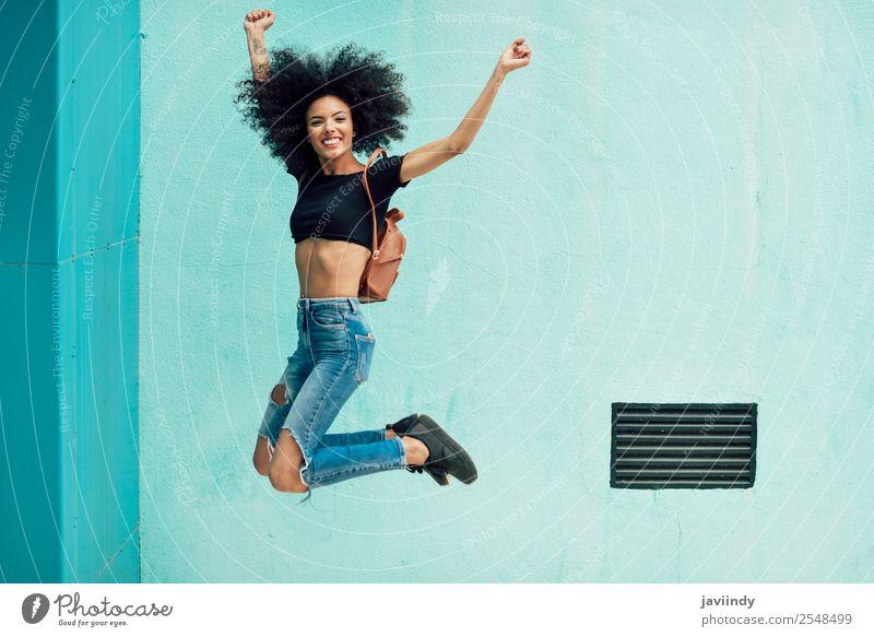 Junge gemischte Frau mit Afrohaar, die im Freien springt. Lifestyle Stil Glück Haare & Frisuren Gesicht Mensch feminin Junge Frau Jugendliche Erwachsene 1