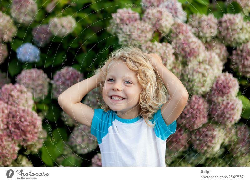 Süßes kleines Kind mit langen Haaren im Garten Glück schön Gesicht Sommer Mensch Baby Junge Mann Erwachsene Kindheit Hand Umwelt Natur Pflanze Blume blond