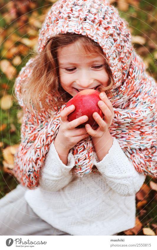 Kind Mädchen isst frischen Apfel im Herbstgarten Frucht Lifestyle Freude Spielen Garten Kindheit Natur Wärme Blatt Wald Schal Lächeln Fröhlichkeit lustig