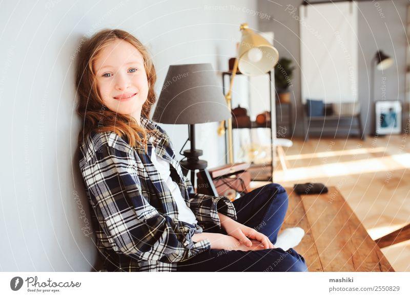 fröhliches Kind Mädchen sitzt auf dem Tisch zu Hause Lifestyle Erfolg Schule lernen Schulkind Kindheit Buch Schreibstift Lächeln schreiben sitzen klug Interesse