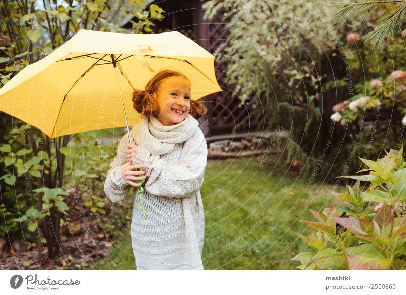 glückliches Kind Mädchen, das sich unter dem Regenschirm versteckt. Lifestyle Freude Glück Garten Kindheit Natur Herbst Wetter Park Pullover Tropfen lustig nass