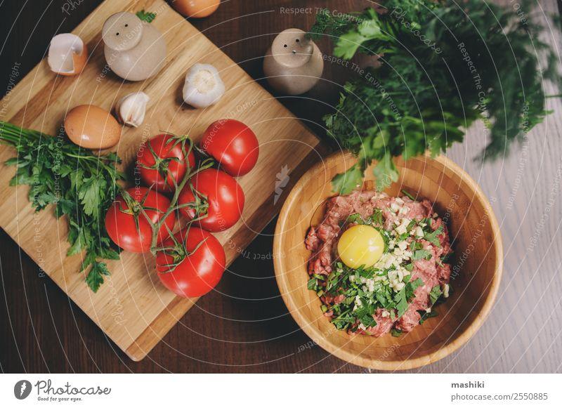 Rohes Hackfleisch mit Ei, Kräutern und frischen Tomaten Fleisch Gemüse Ernährung Teller Schalen & Schüsseln Küche Rindfleisch Ball Brotlaib vorbereiten