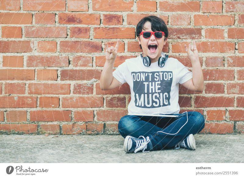 Kind mit Kopfhörern, die mit einem digitalen Tablett verbunden sind. Lifestyle Freude Spielen Entertainment Musik Headset MP3-Player Technik & Technologie