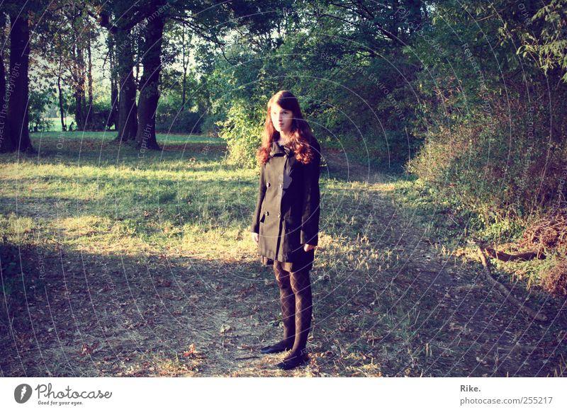 Irgendwo in der Mitte tut's weh. Mensch Junge Frau Jugendliche 1 18-30 Jahre Erwachsene Umwelt Natur Herbst Baum Gras Wald Bekleidung Mantel Strumpfhose brünett