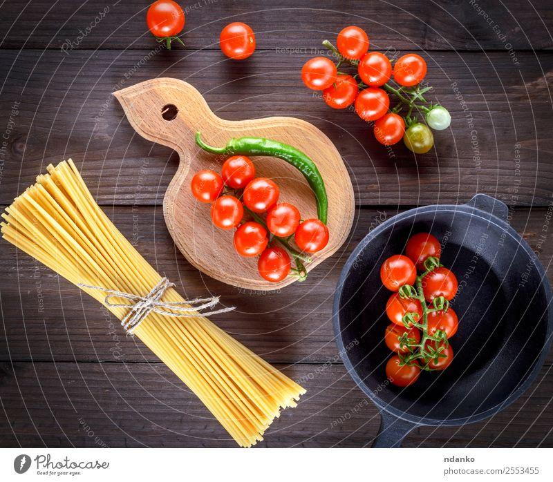 rohe Spaghetti und rote Kirschtomaten Gemüse Teigwaren Backwaren Abendessen Pfanne Tisch Holz frisch gelb weiß Spätzle Lebensmittel Hintergrund Tomate