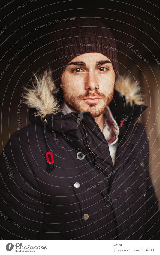 Porträt eines attraktiven Mannes Lifestyle Stil Haus Mensch Junge Erwachsene Wärme Mode Mantel Piercing Hut Vollbart alt Coolness Erotik trendy modern stark