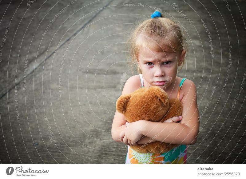 trauriges kleines Mädchen hält Spielzeug mit ihren Händen Gesicht Kind Mensch Frau Erwachsene Kindheit Straße blond Denken Traurigkeit niedlich Gefühle Sorge