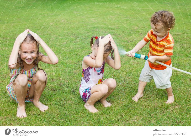 Glückliche Kinder gießen ein Wasser. Freude Freizeit & Hobby Spielen Sommer Haus Garten Mensch Junge Mann Erwachsene Schwester Familie & Verwandtschaft Kindheit