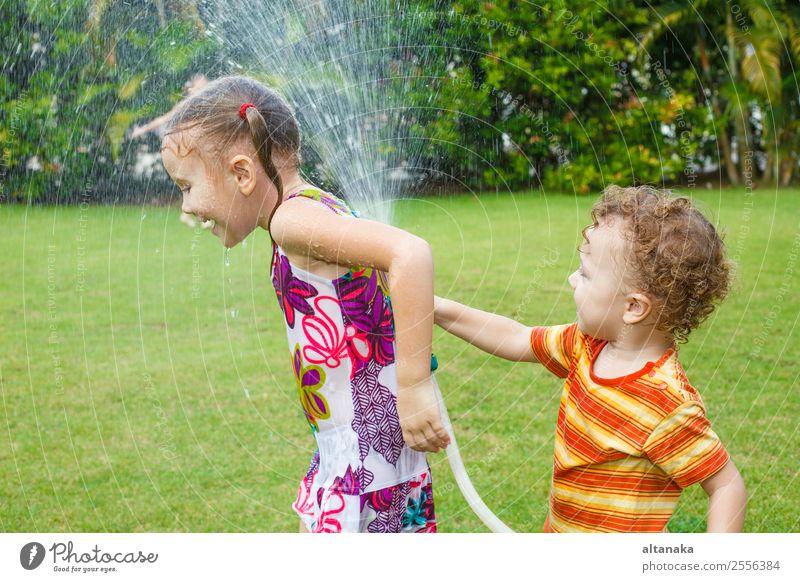 Der kleine Junge gießt ein Wasser aus einem Schlauch bei ihrer Schwester. Freude Glück Freizeit & Hobby Spielen Sommer Haus Garten Kind Mensch Mann Erwachsene