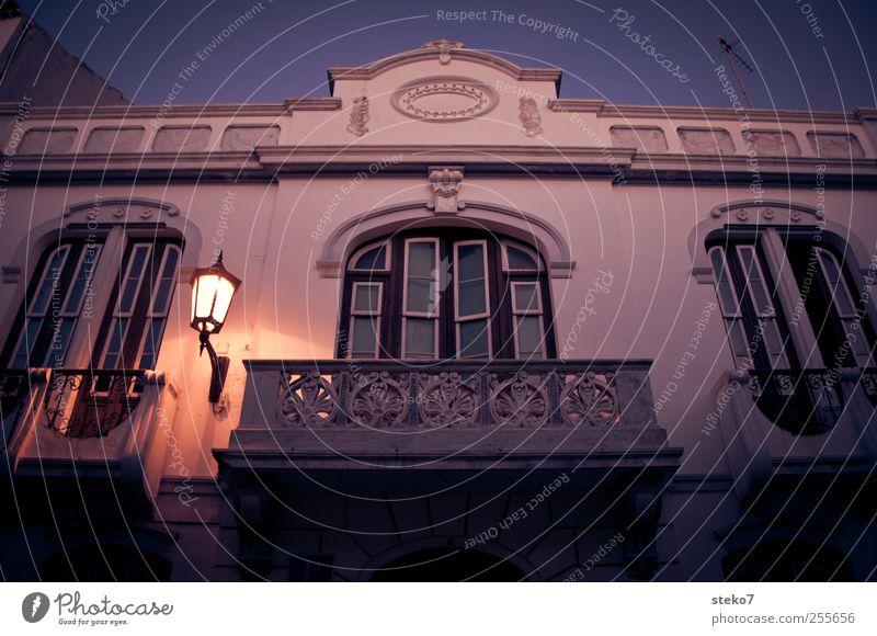 spanischer Balkon blau weiß rot ruhig Haus dunkel Fenster Architektur Fassade Straßenbeleuchtung Wolkenloser Himmel