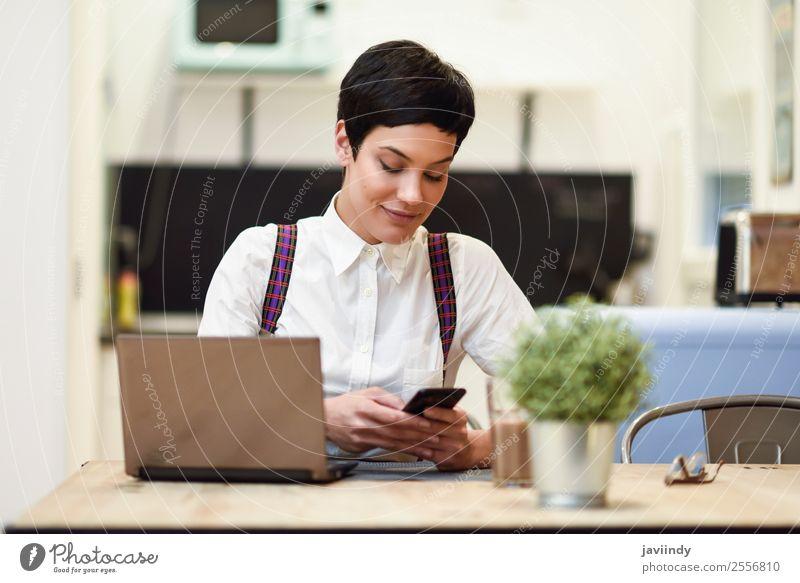 Junge Frau mit sehr kurzem Haarschnitt und Smartphone Lifestyle Stil Glück schön Haare & Frisuren Haus Schreibtisch Arbeit & Erwerbstätigkeit Business Telefon