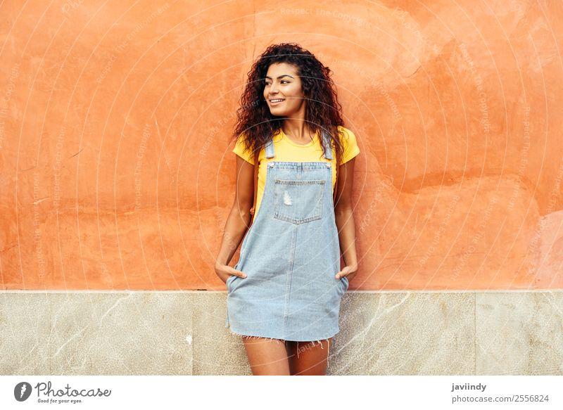 Lächelndes arabisches Mädchen mit schwarzer lockiger Frisur, die nach links zeigt. Lifestyle Stil Glück schön Haare & Frisuren Gesicht Tourismus Mensch feminin