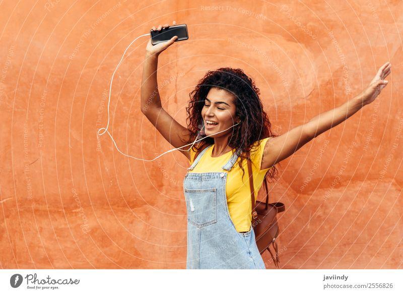 Glückliches arabisches Mädchen, das Musik hört und im Freien tanzt. Lifestyle Stil schön Haare & Frisuren Telefon PDA Technik & Technologie Mensch feminin