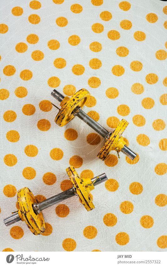 Gelbe antike Gewichte auf einem Polka-Punkttuch Lifestyle Sport Fitness Sport-Training Metall Stahl Rost Diät alt sportlich frei stark Kraft beweglich