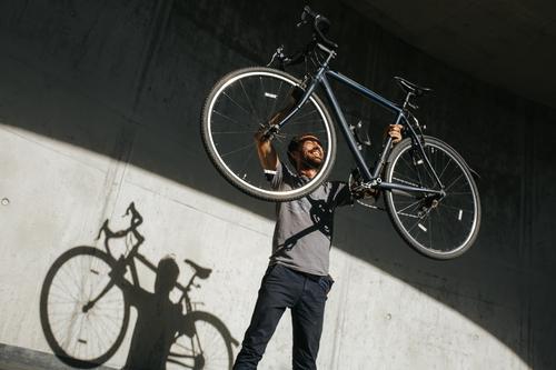 Mann hebt sein Fahrrad in die Höhe Lifestyle Freude Leben Freizeit & Hobby Ferien & Urlaub & Reisen Ausflug Freiheit Sommer Fitness Sport-Training Fahrradfahren
