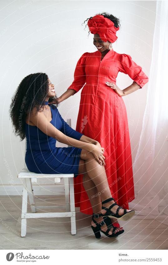 Arabella und Apolline Stuhl Raum Gardine feminin Frau Erwachsene 2 Mensch Kleid Damenschuhe Kopftuch festhalten lachen Blick sitzen stehen Fröhlichkeit schön