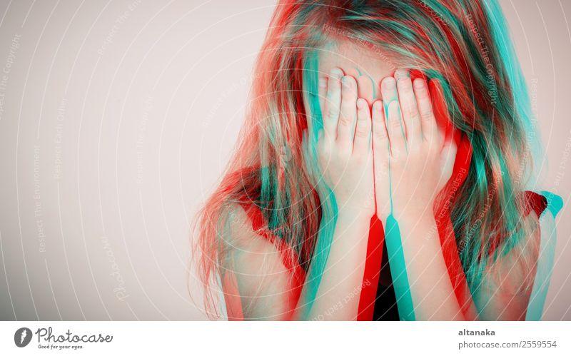 Porträt eines traurigen blonden kleinen Mädchens, das tagsüber im Freien an einer Mauer sitzt. Konzept der Traurigkeit. Foto im Glitched-Stil. Gesicht Kind