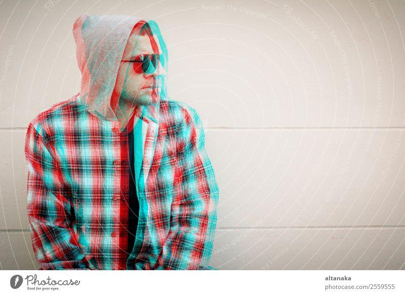 Porträt eines traurigen Mannes mit Sonnenbrille sitzt im Freien in der Nähe des Hauses in der Tageszeit. Konzept der Traurigkeit. Glitched Stil Foto. Lifestyle