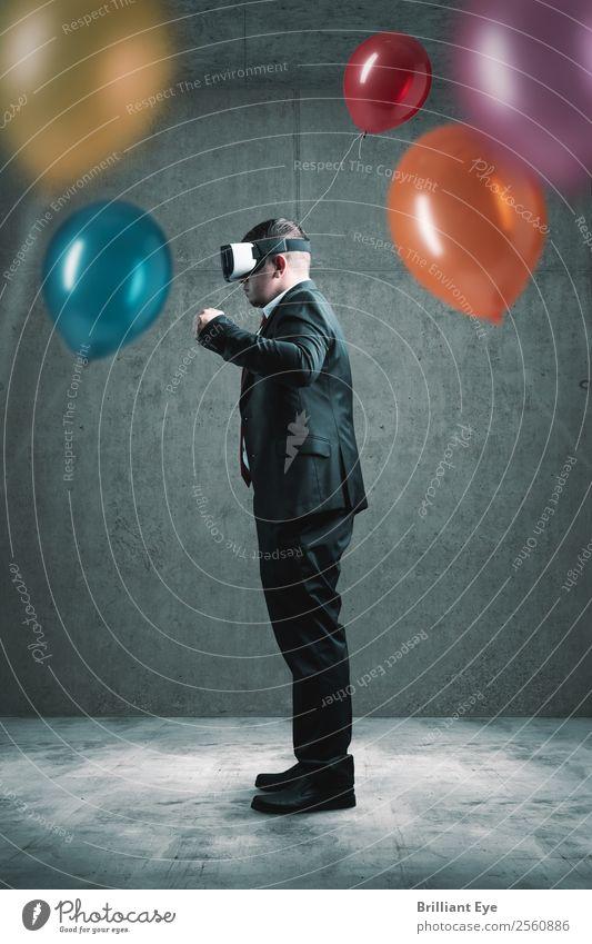 Geschäftsmann steht mit VR-Headset auf Betonboden und hält roten Ballon in der Hand vor vielen anderen bunten Luftballons Lifestyle Freude Freizeit & Hobby
