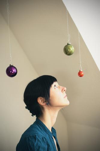 °°° feminin Junge Frau Jugendliche Erwachsene 1 Mensch 18-30 Jahre schwarzhaarig Weihnachtsdekoration Christbaumkugel Kugel Blick blau grün violett Neugier