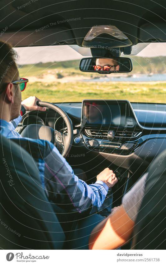 Junger Mann fährt ein Auto Lifestyle Ferien & Urlaub & Reisen Ausflug Abenteuer Technik & Technologie Mensch Frau Erwachsene Paar Arme Hand Gras Wiese Küste