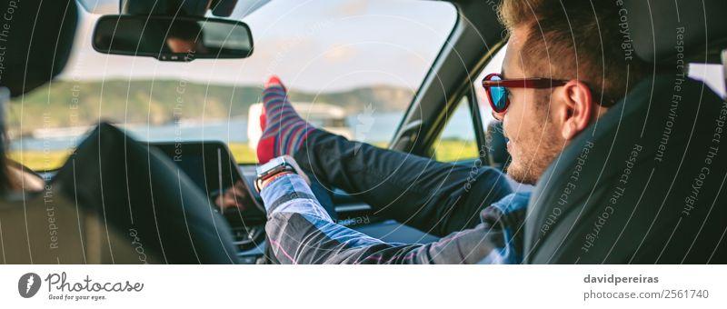 Junger Mann ruht mit den Füßen auf und setzt sich auf das Auto. Lifestyle Freude Glück Erholung Freizeit & Hobby Ferien & Urlaub & Reisen Ausflug Abenteuer