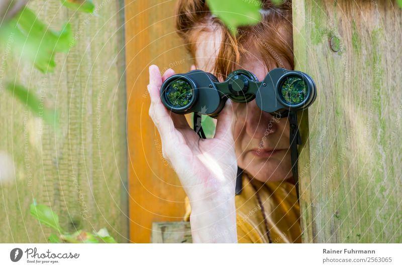 """eine Frau beobachtet durch ein Fernglas Mensch feminin Erwachsene Kopf Hand 1 Natur Garten rothaarig beobachten Neugier Interesse Rache """"Gartenzaun Zaun Spion"""