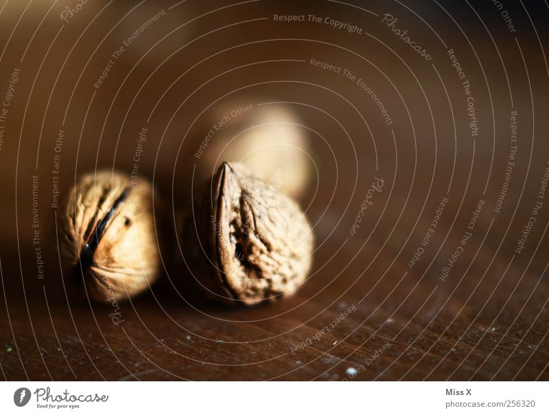 drei Nüsse für Aschenbrödel Lebensmittel Ernährung braun Nuss Nussschale Walnuss Hülle Holz Holzplatte hart Farbfoto Gedeckte Farben Innenaufnahme Nahaufnahme