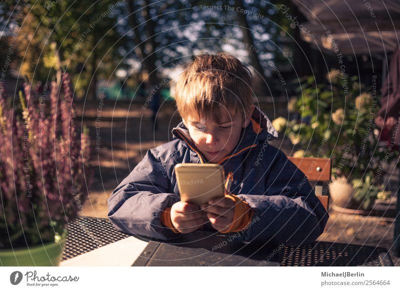 Kind mit Smartphone sitzt draussen im Herbst Mensch maskulin Junge Kindheit 1 3-8 Jahre Spielen Jacke herbstlich kalt frisch Außenaufnahme PDA Telefon Internet