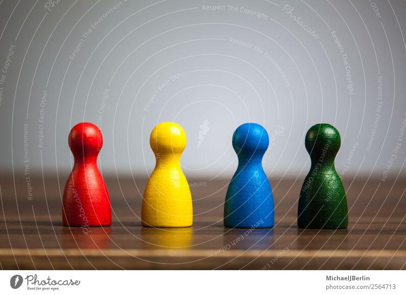 Vier Spielfiguren auf Tisch in diversen Farben Spielen Business blau mehrfarbig gelb grün rot Symbole & Metaphern Vielfältig Verschiedenheit different