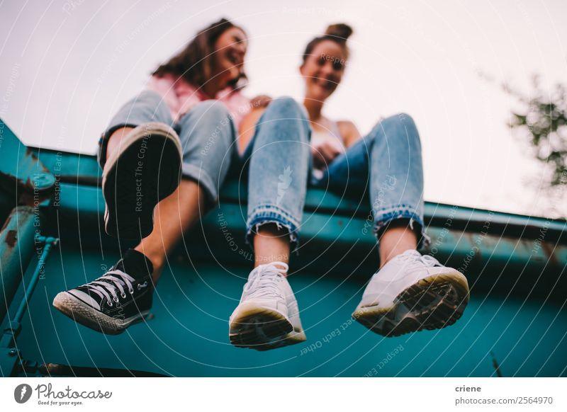zwei freche Frauen, die auf einem großen Behälter sitzen. Lifestyle Freude Glück sprechen Mensch Erwachsene Freundschaft Jeanshose Turnschuh lachen lustig