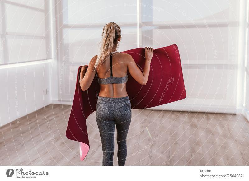 junge Frau, die eine Fitnessmatte für eine Übung vorbereitet. Lifestyle schön Körper Wellness Erholung Sport Yoga Mensch Erwachsene Band Unterwäsche Bewegung