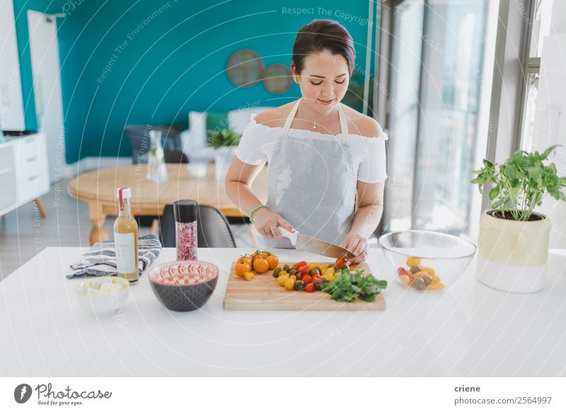 junge Frau bereitet gesunden Salat in der Küche zu Gemüse Ernährung Essen Vegetarische Ernährung Teller Lifestyle Freude Glück Gesundheitswesen Haus Tisch