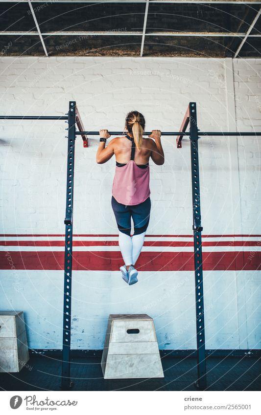 junge kaukasische Frau beim Pull-up in der Turnhalle Körper Sport Mensch Erwachsene Fitness muskulös stark Kraft Training Klimmzüge Athlet üben