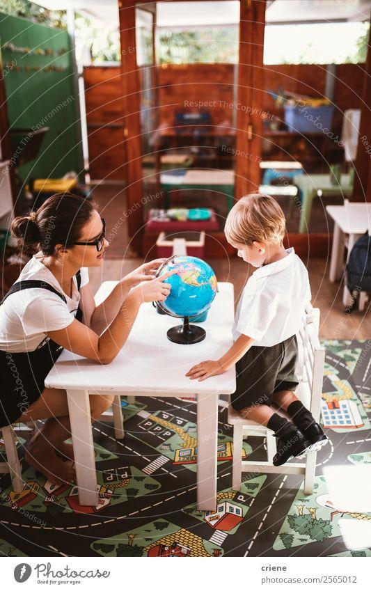 kleiner Junge, der mit der Lehrerin im Klassenzimmer studiert. Glück Schreibtisch Kind Schule Klassenraum Mensch Frau Erwachsene Mann Buch Globus sitzen
