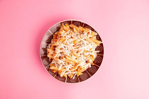 Teller mit Makronen in buntem Hintergrund Fleisch Käse Kräuter & Gewürze Mittagessen Abendessen Diät Tisch Restaurant Holz frisch lecker grün rot Makkaroni