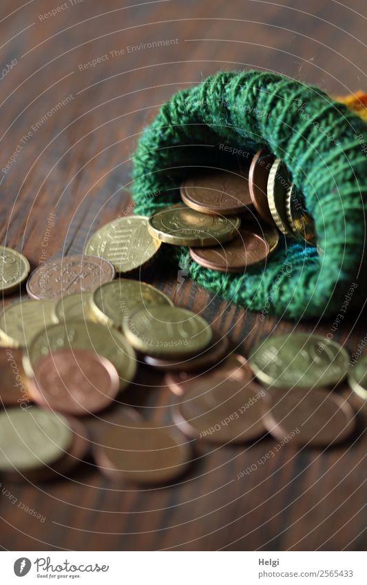 gestrickte Wollsocke als Sparstrumpf, gefüllt mit Geldmünzen Holz bezahlen kaufen liegen sparen außergewöhnlich einzigartig braun grün Sicherheit Ausdauer Armut
