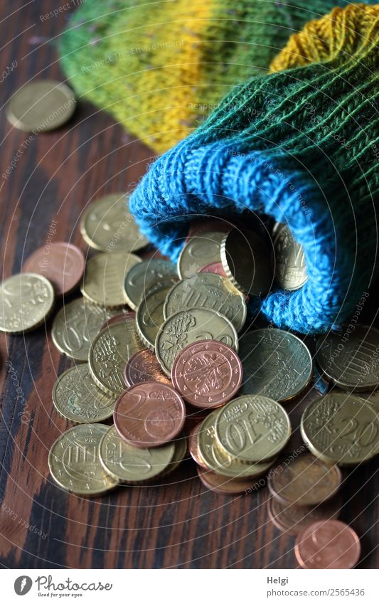 gestrickte bunte Wollsocke als Sparstrumpf mit Geldmünzen auf einem Holztisch Strümpfe Euro Cent liegen Armut außergewöhnlich klein rund braun gelb grün