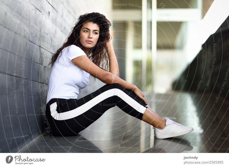 Afrikanische Frau mit schwarzer lockiger Frisur sitzend Lifestyle Stil schön Haare & Frisuren Gesicht Sport Mensch feminin Junge Frau Jugendliche Erwachsene 1