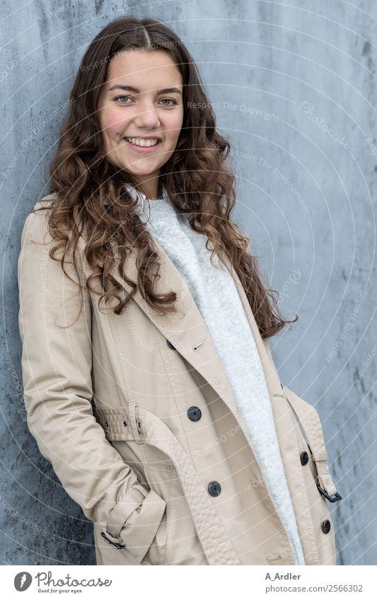 Junge Frau im Mantel Mensch Platz Mauer Wand Mode Bekleidung Stoff brünett langhaarig Locken Lächeln Coolness Freundlichkeit Fröhlichkeit schön blau braun grau