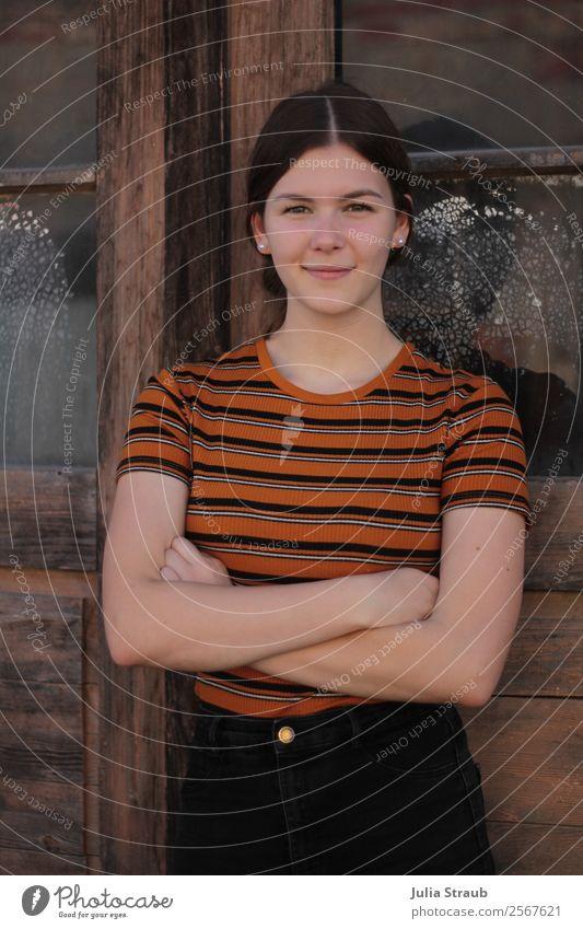 Junge Frau Holztür Glas feminin Jugendliche 1 Mensch 13-18 Jahre Fenster Tür T-Shirt Hose brünett langhaarig Zopf Lächeln stehen Coolness schön retro braun